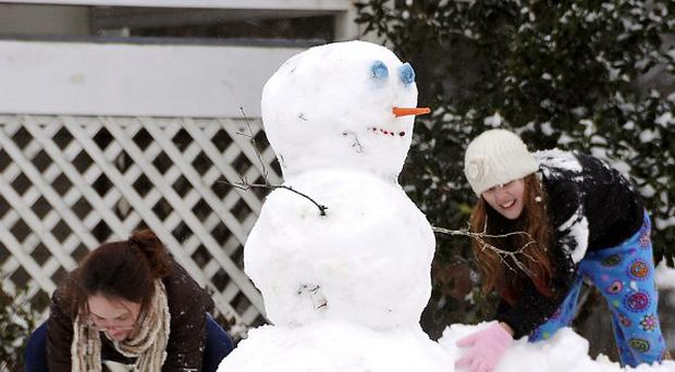 Barrow County residents make a snowman as a winter snow storm blows into Euharlee, Georgia (AP)