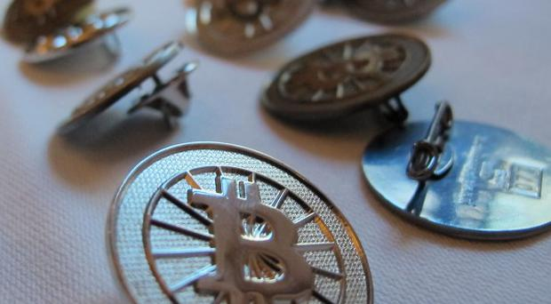 Bitcoin buttons are displayed on a table at the Inside Bitcoins conference in Berlin (AP)