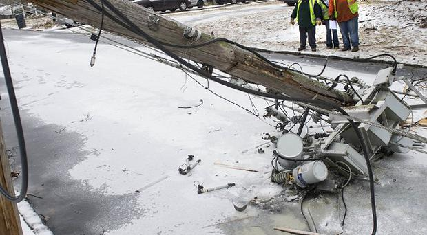 Workers inspect a transformer downed by the winter storm in Doraville, Georgia (AP)