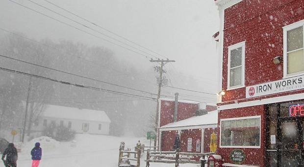 Customers walk home as snow falls at the Iron Works Market in Gilmanton, New Hampshire (AP)