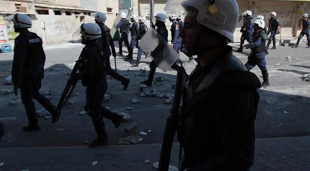 Riot police officers move towards anti-government protesters during clashes in Bahrain (AP)