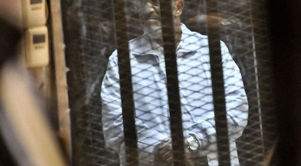 Former president Mohammed Morsi inside a glass defendant's cage during his trial on charges related to the prison breaks at the height of the 2011 uprising (AP)