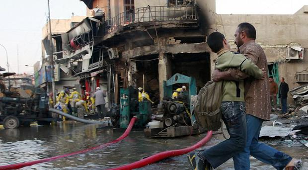 A man helps his son at the site of a car bomb attack in Baghdad (AP)