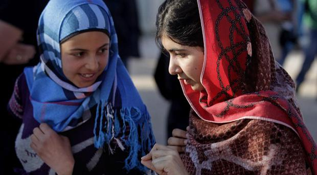 Malala Yousafzai, right, speaks to Syrian refugee Mzoun Mlihan, 16, during her visit to Zaatari refugee camp (AP)