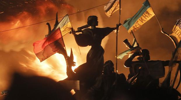 Monuments to Kiev's founders burn as anti-government protesters clash with riot police in Independence Square (AP)
