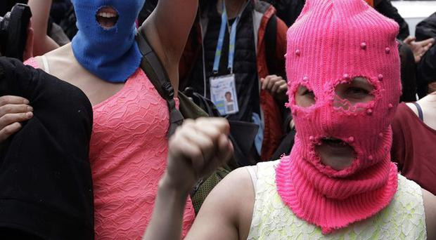 Pussy Riot members Nadezhda Tolokonnikova, in the blue balaclava, and Maria Alekhina, in the pink balaclava, after they were released from a police station (AP)