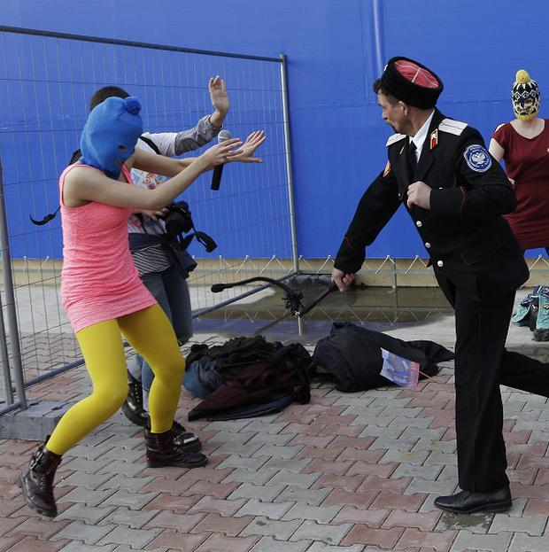 A Cossack militiaman attacks members of the punk group Pussy Riot in Sochi (AP)
