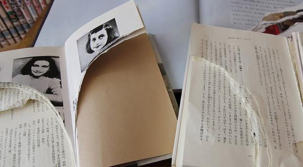 Ripped copies of Anne Frank's Diary of a Young Girl and related books are shown at Shinjuku City Library in Tokyo (AP)
