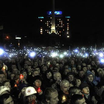 People turn on mobile phones and flash lights as a body of an anti-government protester killed in clashes with police is brought to Independence Square in Kiev (AP)