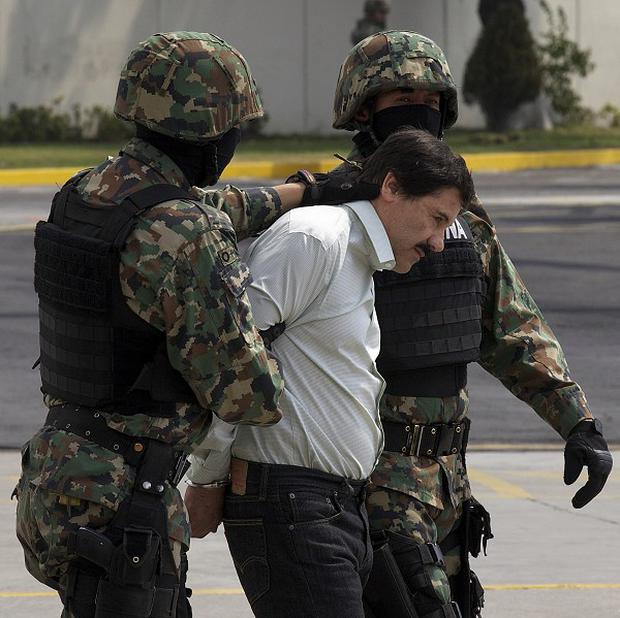 "Joaquin ""El Chapo"" Guzman is escorted to a helicopter in handcuffs by navy marines in Mexico City (AP)"