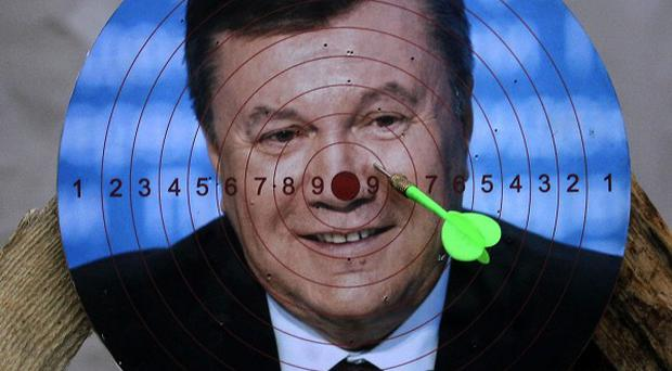 A portrait of Ukraine's embattled president Viktor Yanukovych is used for a game of darts at Independence Square in Kiev (AP)