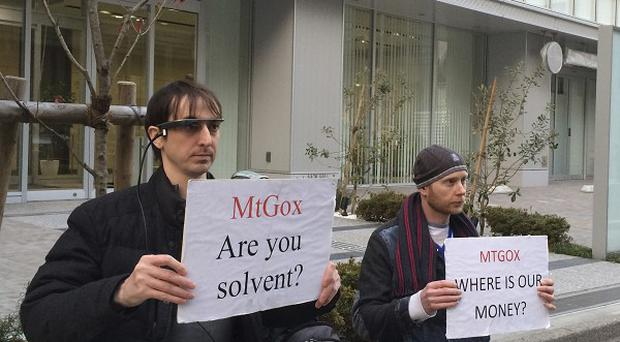 London bitcoin trader Kolin Burges, right, and an American called Aaron hold protest signs outside the Tokyo office tower housing Mt Gox (AP)