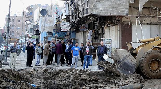 Civilians clear the aftermath of an earlier car bomb attack in the crowded commercial area of Karrada, Baghdad (AP)