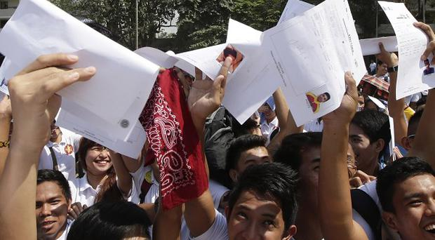 Students from the Polytechnique University of the Philippines cheer as they wave their
