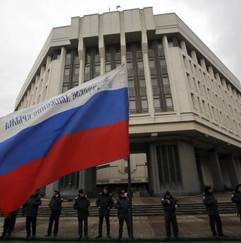 Ukrainian police secure the entrance of a seized local government building in Simferopol, Crimea, bearing a Russian flag (AP)