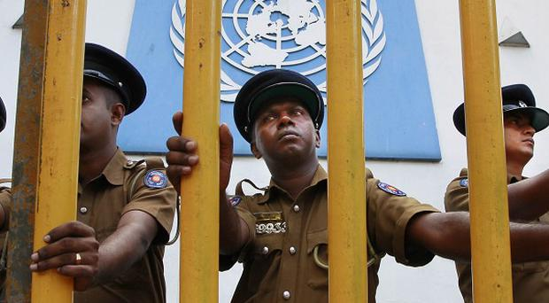 Sri Lankan police officers secure a barricade outside the UN office during a protest by National Rights Organisation members in Colombo (AP)