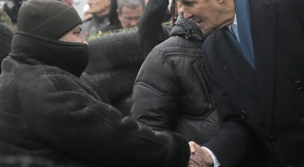 John Kerry, right, shakes hands with a Ukrainian protester at the barricades in Kiev (AP)