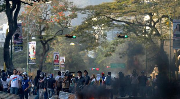 Demonstrators stand behind a barricade during an anti-government protests in Caracas, Venezuela a year after the death of Hugo Chavez (AP)