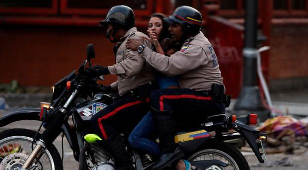 Police detain an anti-government demonstrator during clashes in Caracas (AP)
