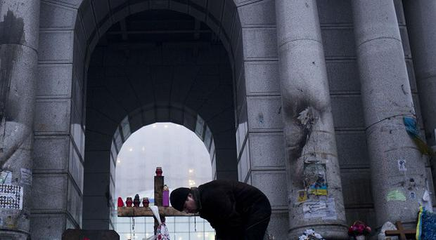 A man arranges candles at a memorial to victims of February's clashes in Kiev's Independence Square (AP)