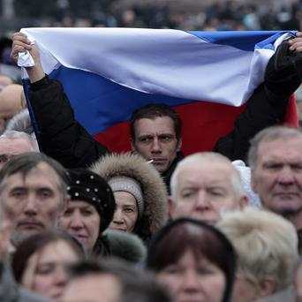 A man holds up a Russian flag during a pro-Russian rally at a central square in Donetsk, Ukraine (AP)