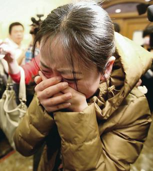 A relative of a passenger onboard Malaysia Airlines flight MH370 breaks down in tears;