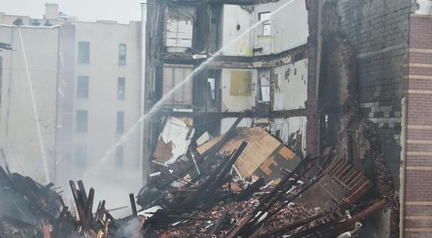 Firefighters continue to spray water on the smouldering debris from an explosion in Harlem (AP)