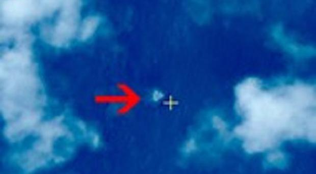 This satellite image shows floating objects at sea next to the red arrow which was added by the source (AP/Chinese State Administration of Science, Technology and Industry for National Defence)