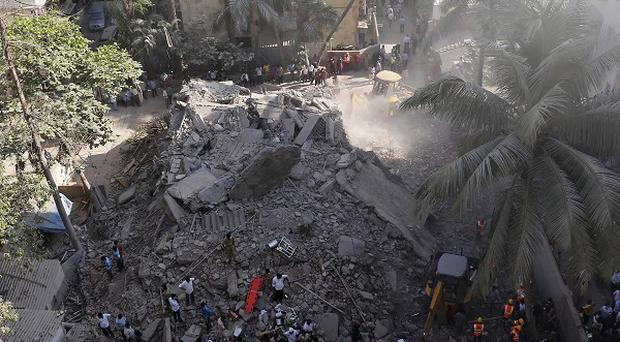Rescue workers search for survivors in the debris of a building that collapsed in Mumbai, India (AP)
