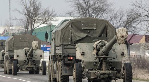 A convoy of trucks towing artillery cannons at a security checkpoint in Crimea (AP)