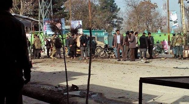 Afghan police and civilians inspect the site of a suicide attack (AP)