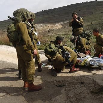 A wounded Israeli soldier is treated after a roadside bomb hit a patrol. (AP Photo/Jinipix)