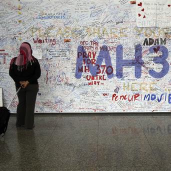 A woman reads messages for passengers aboard a missing Malaysia Airlines plane at Kuala Lumpur International Airport in Sepang, Malaysia (AP)