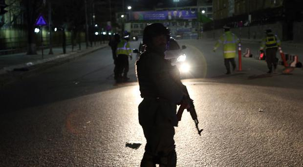 Afghan police stand guard at the site of a gun battle at the Serena Hotel in Kabul (AP)