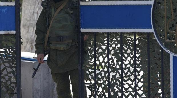 A pro-Russian soldier guards the gate of the Ukrainian navy headquarters in Sevastopol, Crimea. (AP)