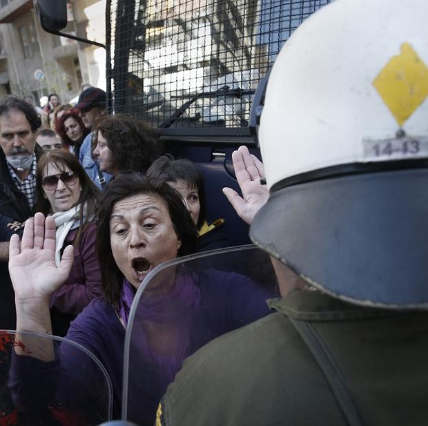 Protesting civil servants confront riot police in central Athens. (AP)
