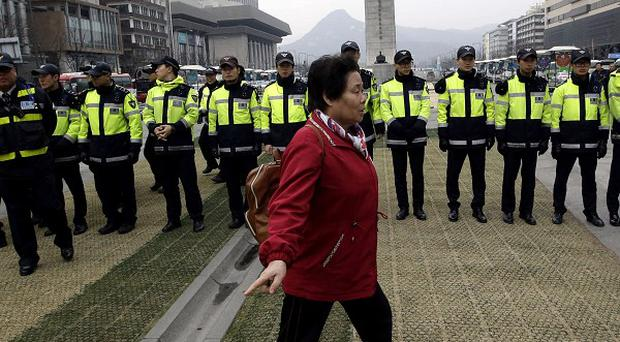 A woman walks in front of police officers blocking protesters during an anti-North Korea rally in Seoul (AP)
