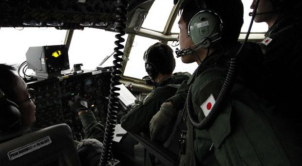 A Japanese Air Self-Defence Force crew scan the search area aboard a C130 aircraft (AP)