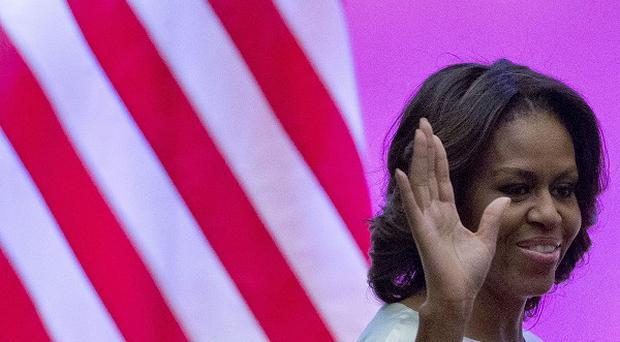 Michelle Obama waves to students before she gives a speech at Peking University in Beijing (AP)