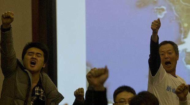 Angry relatives of Chinese passengers aboard the missing jet after Malaysian officials left a briefing in Beijing (AP)