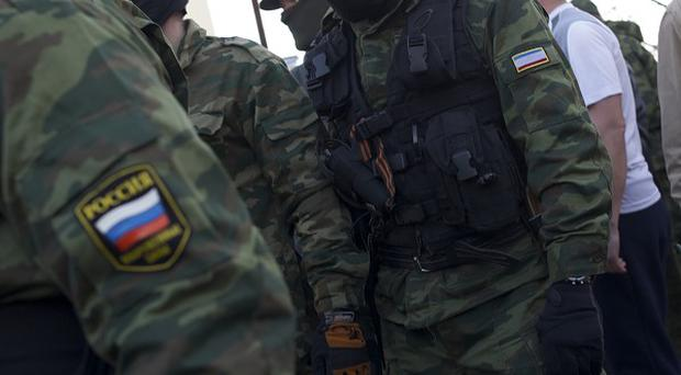Soldiers with Russian and Crimean patches and pro-Russian militia members guard outside the Belbek airbase (AP)