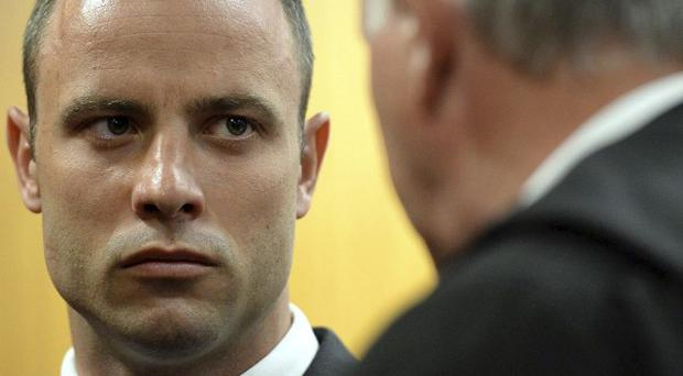 Oscar Pistorius talks to his defence lawyer Barry Roux before proceedings at the high court in Pretoria, South Africa (AP)