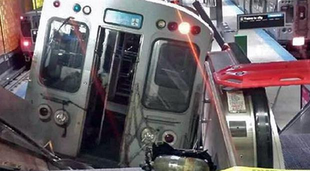 A Chicago Transit Authority train car rests on an escalator at the O'Hare Airport station after it derailed (AP/NBC Chicago, Kenneth Webster)