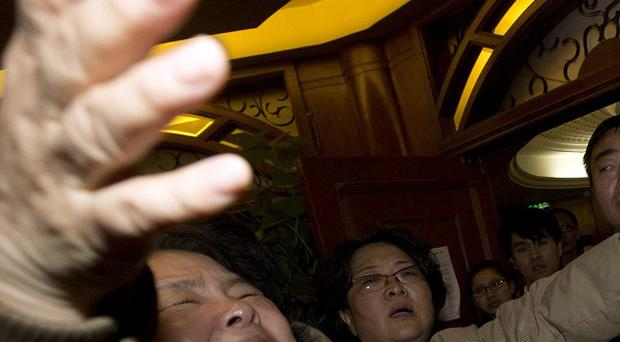 A distraught relative of a Chinese passenger is told that the missing Malaysia Airlines plane crashed into the Indian Ocean (AP)