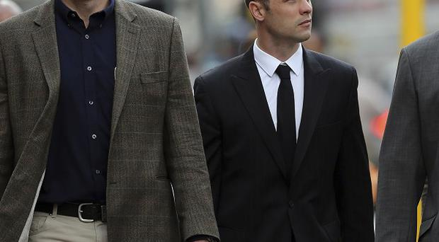 Oscar Pistorius, center, arrives with relatives at the high court in Pretoria (AP)