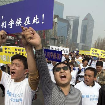 Chinese relatives of passengers on the missing Malaysia Airlines plane march towards the Malaysia embassy in Beijing (AP)