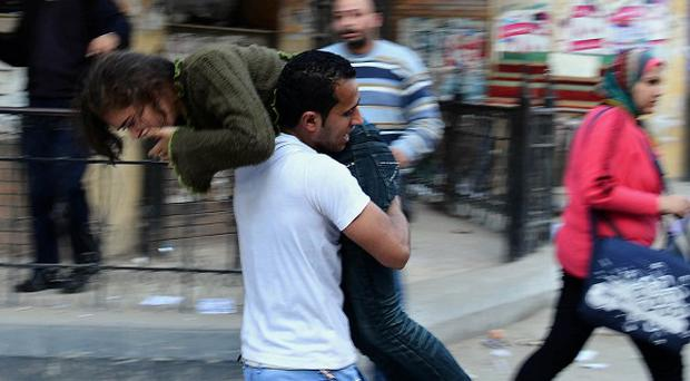 An Alexandria University student carries another after she was injured during clashes between student protesters and the Egyptian security forces (AP)