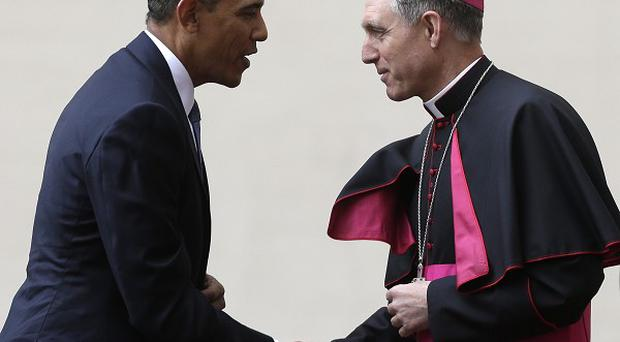 US President Barack Obama is welcomed by Archbishop George Gaenswein as he arrives at the Vatican to meet Pope Francis (AP Photo/Alessandra Tarantino)