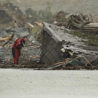 A search and rescue worker carrying a probe peers into the remains of a building on the eastern edge of the massive mudslide (AP)
