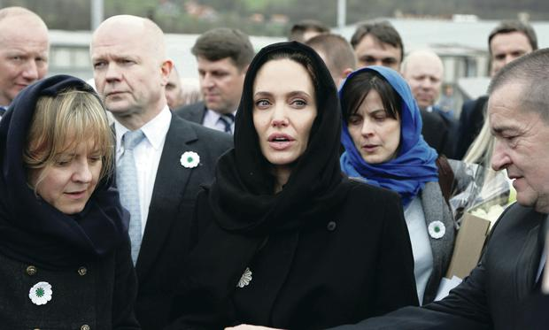 Angelina Jolie (centre) and British Foreign Secretary William Hague (second left) pay their respects to victims at the memorial centre of Potocari near the eastern Bosnian town of Srebrenica y